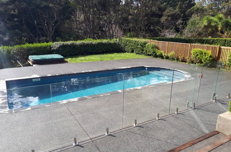 A very clean glass safety fence surrounding a pool area