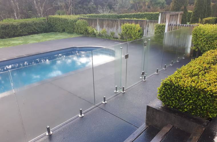 A clean glass fence surrounding a pool area