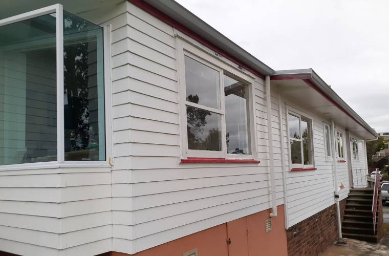 A weatherboard house before it has been cleaned