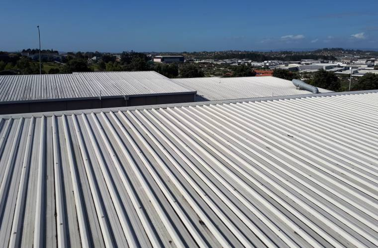 A commercial building with a white corrugated iron roof and a view of the sea