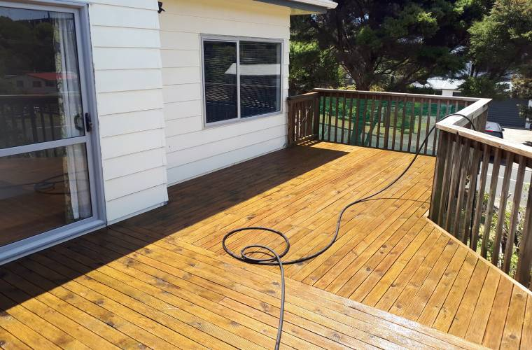 A recently water blasted deck with the hose still in view